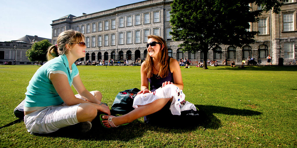 People sitting outside Trinity College, Dublin